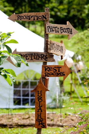 A very cool and unique wedding sign showing guests directions to various areas and a tent in the background  Stock Photo