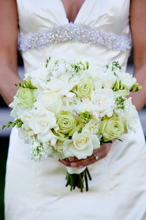 a bride holding a green and white wedding bouquet of flowers photo