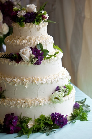 wedding cake: A multi level wedding cake with purple and white flowers