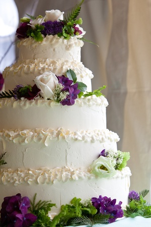 A multi level wedding cake with purple and white flowers