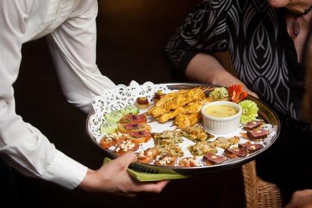 결혼식이나 다른 음식을 장만 이벤트 기간 동안 고객 전채를 제공하는 웨이터