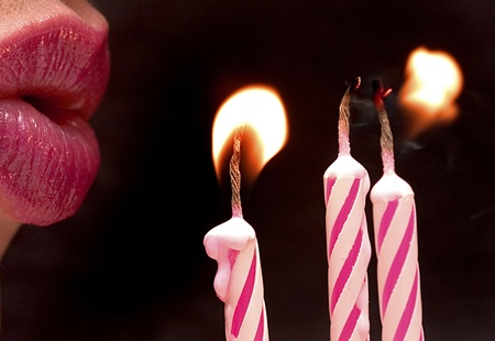 close-up of lips blowing out pink candles