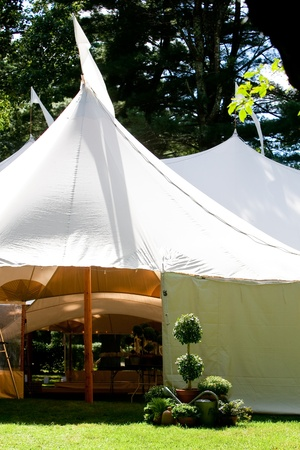 a large white wedding tent set up outside for a catered event Imagens