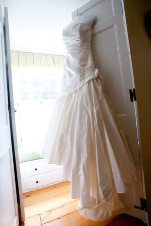 a white wedding dress hanging from a door ready for the bride