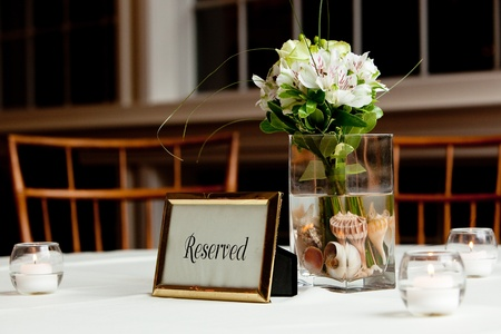 a wedding bouquet in a vase filled with water and sea shells on a reserved table Stock Photo - 13057953