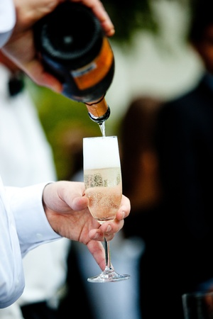 alcohol server: a waiter pouring champagne into a glass for a toast