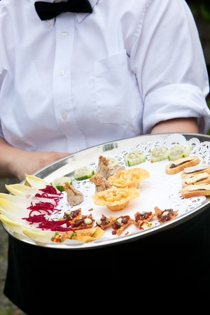 person appetizer: A waiter serving appetizers during a catered wedding or other banquet funtion Stock Photo