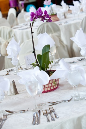 A purple orchid flower centerpiece on a white wedding table photo