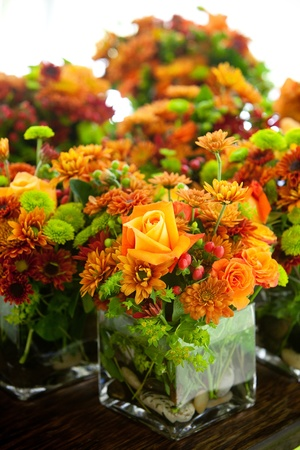 A Group Of Wedding Centerpieces In Glass Jars Orange And Green