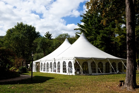 a white wedding tent set up outside for an outdoor reception