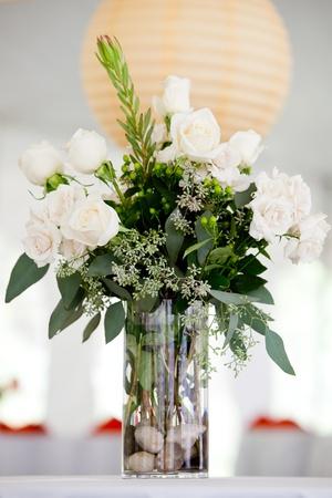 een grote witte bruiloft middelpunt op een tafel, witte rozen