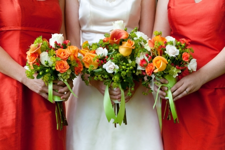 bridal bouquet: three wedding bouquets being held by a bride and her bridesmaids