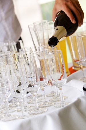 pours: a waiter pours champagne into wine glasses during a wedding celebration