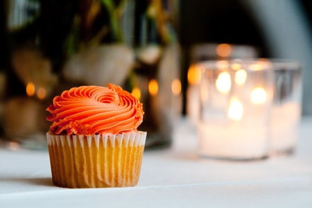 a single orange cupcake sitting on a table waiting to be eaten photo