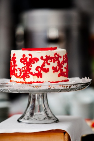 small cake: a small red and white wedding cake on a silver platter Stock Photo