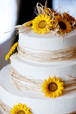 a white wedding cake with yellow flowers and straw