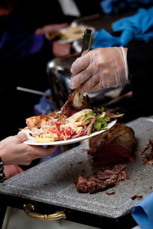 a gloved hand serving wedding food at a catered event Stock Photo - 13057972