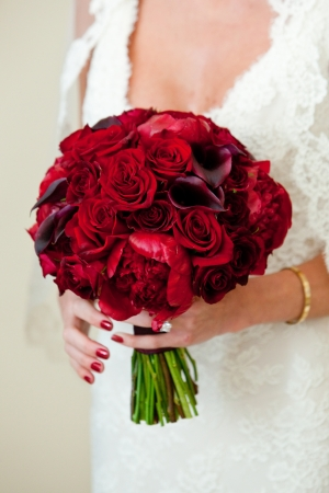 bridal dress: a bride holding her beautiful red flower and rose bouquet