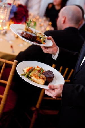 a waiter serving plates of food at a catered wedding