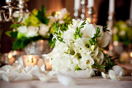 a white wedding bouquet on a dinner table during a reception  shallow depth of field