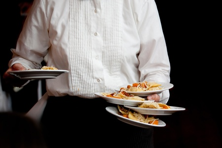 a server wearing a white shirt with dinner on white plates photo
