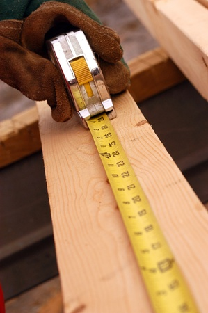 A carpenter using a tape measure, building a house