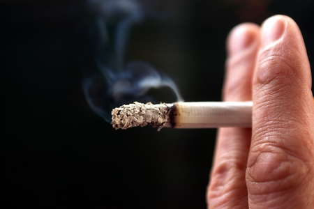 a close-up of fingers holding a cigarette