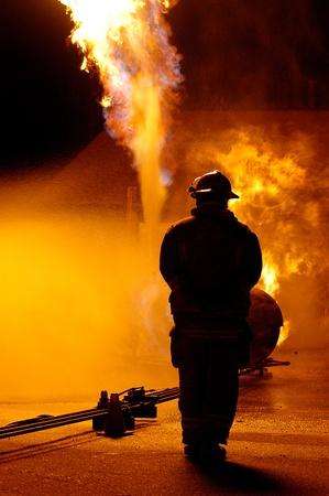 resplandor: un solitario vigilante de los bomberos un incendio. El agua se pulveriza para contener el fuego Foto de archivo