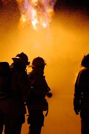 firefighters fight a blaze as a team using a water hose