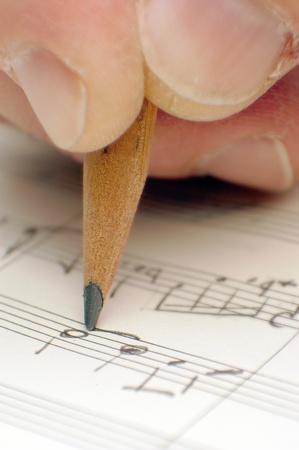 pencil writing: composing musical notes, writing a song with a pencil on paper