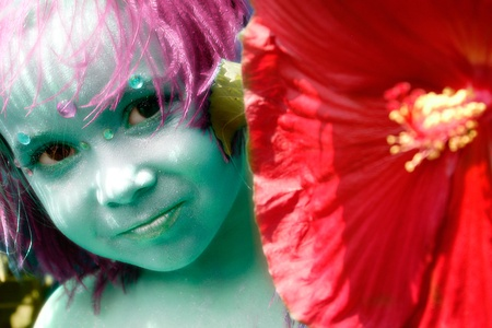 fairy like child looking around a large red flower. She is done in a blue green face makeup Stock Photo