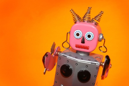 tin: a pink and silver toy maid robot with an orange background Stock Photo