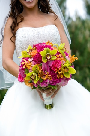 a bridal bouquet in red, pink, green, and orange
