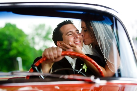 A bride giving her groom a kiss while he sits inside a car and smiles photo