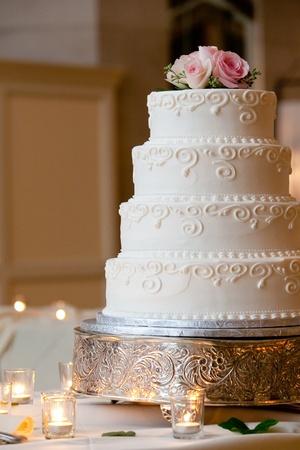 een multi-level witte bruidstaart op een zilveren voet en roze bloemen op de top