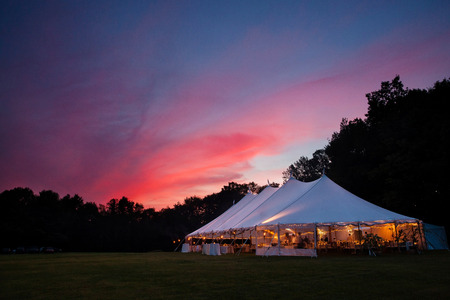 An event tent in a field at sunset during a wedding