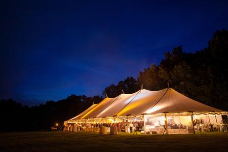 Een evenement tent in een veld in de nacht tijdens een bruiloft. gloeiende vanuit