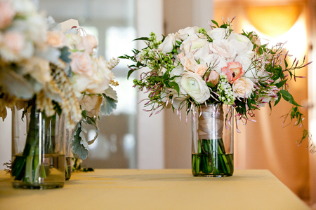 a bridal wedding bouquet in a glass jar before the wedding ceremony, White and pink flowers set down on a table Foto de archivo