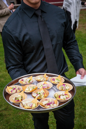 a waiter holding a platter full of wooden bowls with appetizers - wedding catering series