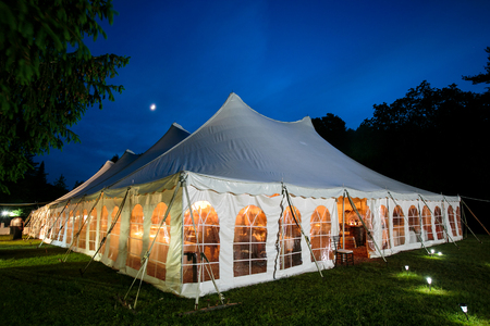 A wedding tent at night with blue sky and the moon. The walls are down and the tent is set up on a lawn - wedding tent series Stockfoto