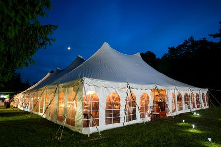 Ein Hochzeitszelt nachts mit blauem Himmel und dem Mond. Die Wände sind runter und das Zelt steht auf einer Wiese - Hochzeitszeltserie