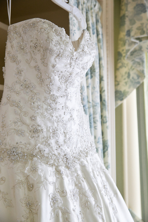 details of a white wedding dress hanging in a room waiting for a bride