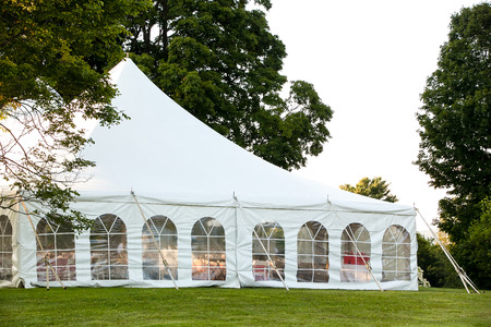 a white wedding tent set up in a lawn surrounded by trees and with the sides down Stok Fotoğraf - 119668655