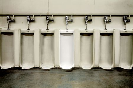 dirty room: One clean white urinal among the dirty ones