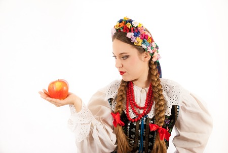tresses: A young beautiful woman with long blonde hair tresses wearing a traditional Polish folk costume and holding an apple