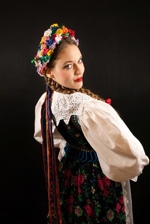 tresses: A young beautiful woman with long blonde hair tresses wearing a traditional Polish folk costume Stock Photo