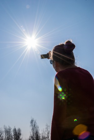 cracow: CRACOW, POLAND - MARCH 20, 2015: A woman watching a partial solar eclipse throught the dark glass in southern Poland