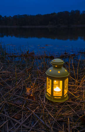evening on a lake with a burning lantern