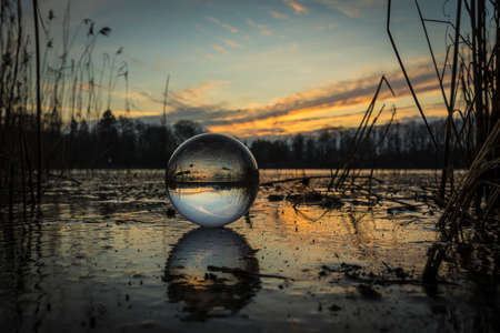 sunset on a icy winter evening seen in a lensball