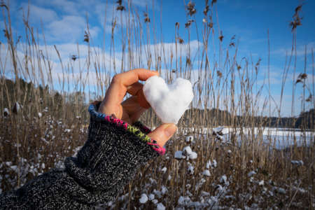 women holding a heart shaped snow ball